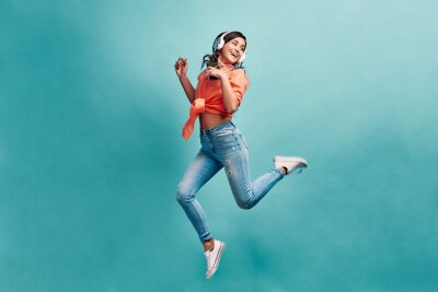 Fototapete Young beautiful energy girl with white headphones listening to music laughs and jump on blue background in studio and looks away.Dressed in an orange shirt and light jeans, holding a phone.