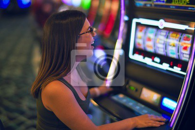 Fototapete Young beautiful woman smiling happy and confident. Sitting with smile on face playing slot machine at casino