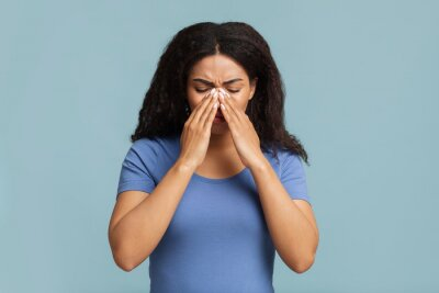 Fototapete Young black woman touching her nose bridge, suffering from rhinitis, grey background