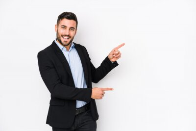 Fototapete Young caucasian business man against a white background isolated excited pointing with forefingers away.