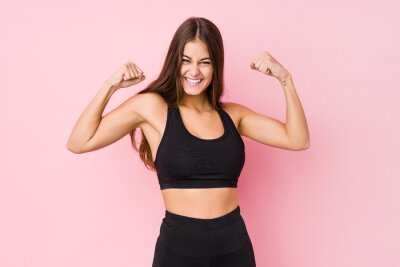 Fototapete Young caucasian fitness woman doing sport isolated showing strength gesture with arms, symbol of feminine power