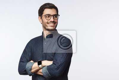 Fototapete Young handsome business man dressed in casual denim shirt with smartwatch on wrist, isolated on gray background