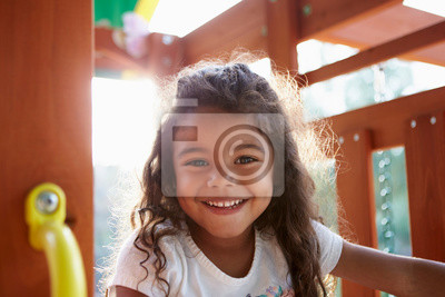 Fototapete Young Hispanic girl playing on a climbing frame in a playground smiling to camera, backlit, close up