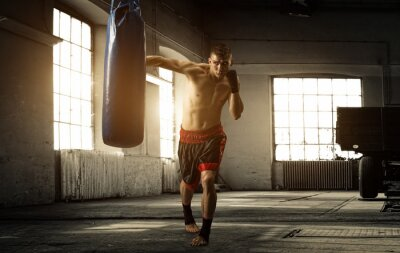 Fototapete Young man boxing workout in an old building