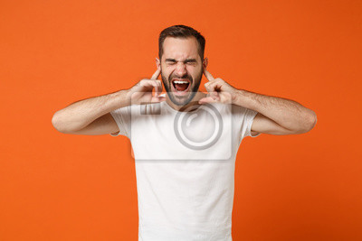 Fototapete Young man in casual white t-shirt posing isolated on bright orange background studio portrait. People lifestyle concept. Mock up copy space. Covering ears with fingers, keeping eyes closed, screaming.