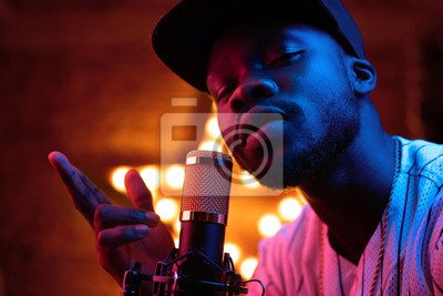 Fototapete Young man with beard and mustaches in baseball cap and t-shirt sing in microphone and look in camera. Pink neon light