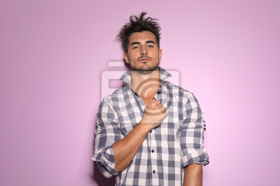 Fototapete Young man with trendy hairstyle posing on color background