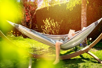 Fototapete Young relaxed girl reading book in hammock in garden at home at bright sunset. Slow living, gadget detox and weekend leisure activity. Quarantine and self isolation period