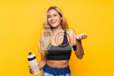 Fototapete Young sport woman with a bottle of water over isolated background
