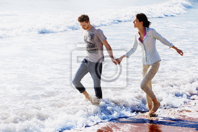 Young White Couple Walking at the Beach