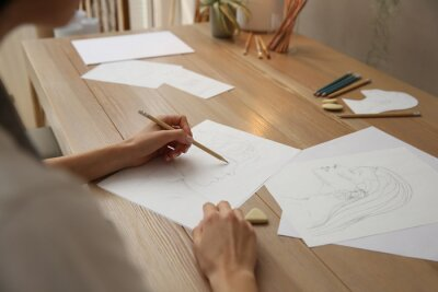 Fototapete Young woman drawing male portrait at table indoors, closeup