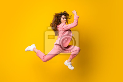 Fototapete Young woman jumping over isolated yellow wall