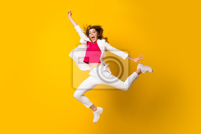 Fototapete Young woman jumping over isolated yellow wall making victory gesture