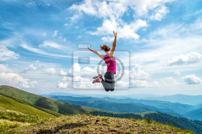 Fototapete Young woman on the top of mountain