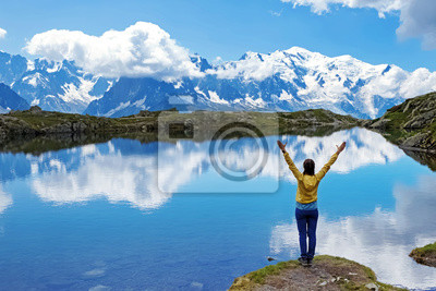Fototapete Young woman standing on the shore of scenic mountain lake in Alps with her hands raised.
