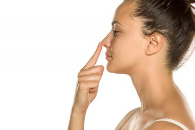 Fototapete young woman touches her nose with her finger on a white background