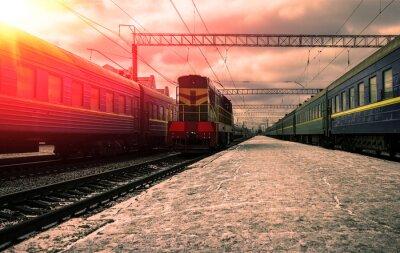 Fototapete Zug in den Strahlen der roten Sonne