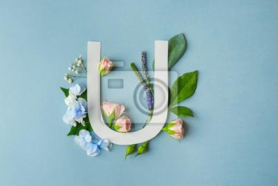 Zusammensetzung mit Buchstaben U und schönen Blumen auf Farbhintergrund