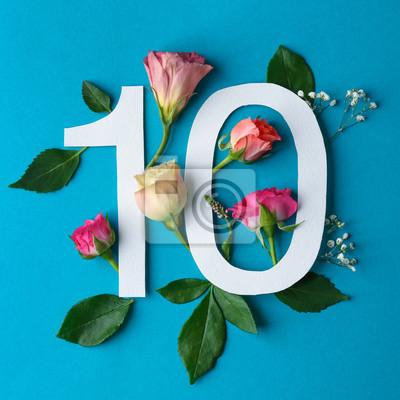 Zusammensetzung mit Nr. 10 und schönen Blumen auf Farbhintergrund