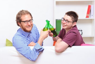 Zwei junge Männer mit Bier auf dem Sofa