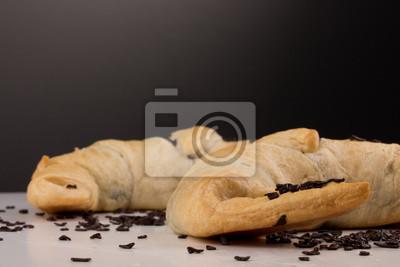 Fototapete zwei Schokoladen-Croissants mit Schokoladenstreuseln vor schwarzem / weißem Hintergrund