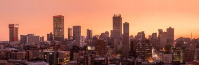 Poster A beautiful and dramatic panoramic photograph of the Johannesburg city skyline, taken on a golden evening after sunset.