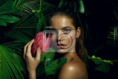 Poster A beautiful tanned girl with natural make-up and wet hair stands in the jungle among exotic plants.