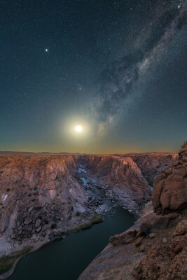 Poster A majestic vertical night sky photograph with the Moon rising below the Milky Way in the deep blue sky, with views of the river and mountains at the Augrabies Falls National Park in South Africa.