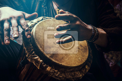 Poster A man playing an ethnic percussion musical instrument jembe. Drummer playing african musicembe
