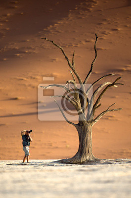 A photographer photographing a tree in Deadvlei, Namibia.