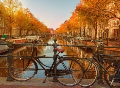 Abend über schöne Amsterdam Kanäle im Herbst. Fahrräder parkten an den Brücken im Vordergrund