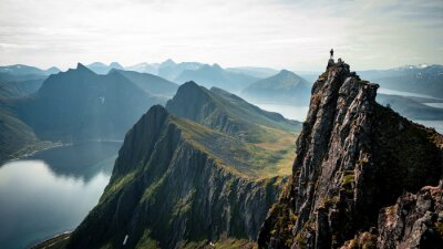 Poster Adventurous man is standing on top of the mountain and enjoying the beautiful view during a vibrant sunset. Taken on top Senja, Norway