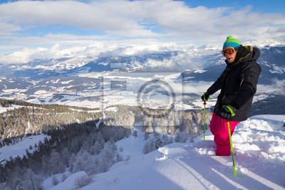 Adventurous skier ready to ski downhill in the backcountry from the top of the mountain