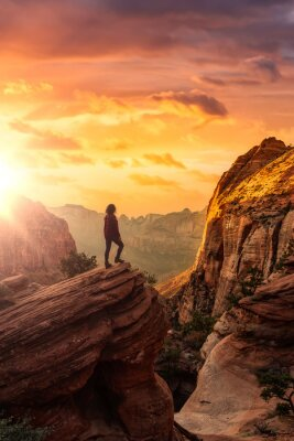 Poster Adventurous Woman at the edge of a cliff is looking at a beautiful landscape view in the Canyon. Sunset Sky Art Render. Taken in Zion National Park, Utah, United States.