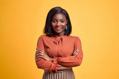 Poster Advertising concept. Confident and smiling young african american woman crossed hands on chest, looking at camera and standing on yellow copy space background.