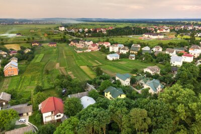 Poster Aerial landscape of small town or village with rows of residential homes and green trees.