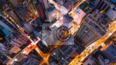 Poster Aerial top view of downtown district  buildings in night city light. Bird's eye view from drone of cityscape metropolis infrastructure, crossing streets with parked cars. Development infrastructure