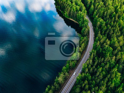Poster Aerial view of road between green forest and blue lake in Finland