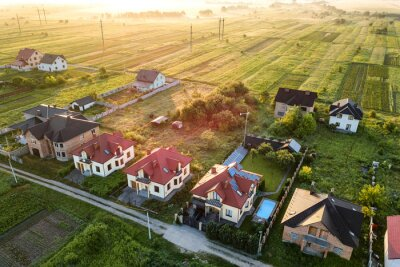 Poster Aerial view of rural residential area with private homes between green fields at sunrise.