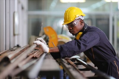 Poster African American mechanic engineer worker is choosing copper tube for sawing while working in coolant factory with copy space