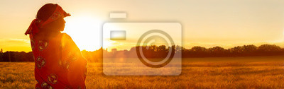 Poster African woman in traditional clothes in field of crops at sunset or sunrise panorama