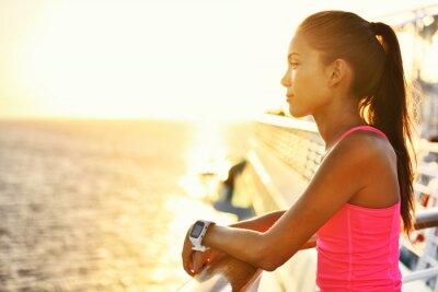 Poster Aktive Frau Entspannung nach Run auf Kreuzfahrtschiff Blick auf das Meer während der Sommerferien. Asian Läufer Mädchen tragen smartwatch Herzfrequenz-Aktivität Monitor leben eine gesunde Lebensweise.