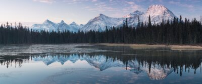 Poster Almost nearly perfect reflection of the Rocky mountains in the Bow River. Near Canmore, Alberta Canada. Winter season is coming. Bear country. Beautiful landscape background concept.