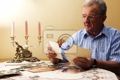 Älterer Mann, der alten Fotografien. Reminisce