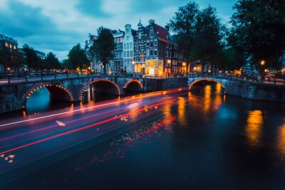 Amazing Light trails and reflections on water at the Leidsegracht and Keizersgracht canals in Amsterdam at evening. Long exposure shot. romantic city trip concept