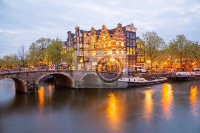 Amsterdam canal, bridge and typical houses, boats and bicycles during evening