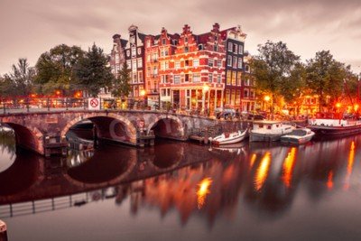 Amsterdam canal, bridge and typical houses, boats and bicycles during evening twilight blue hour, Holland, Netherlands. Used toning