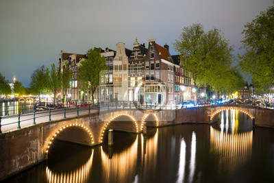 Amsterdam canal, bridge and typical houses during evening twilight blue hour
