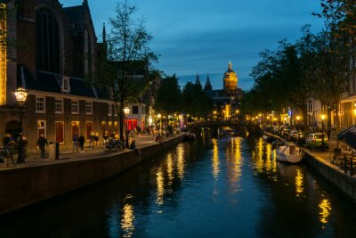 Amsterdam canal evening view with houses and illumination