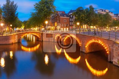 Amsterdam Kanal, Brücke und typische Häuser, Boote und Fahrräder in Abenddämmerung blaue Stunde, Holland, Niederlande.